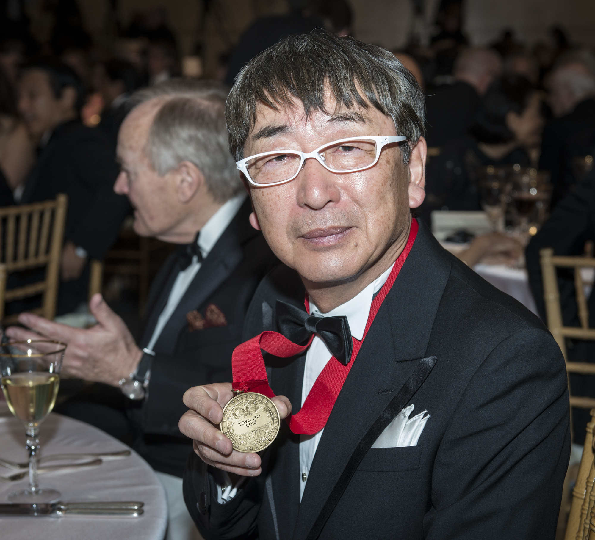 At a ceremony in the John F. Kennedy Library and Museum in Boston, Massachusetts, Japanese architect Toyo Ito received his Pritzker Architecture Prize medal and $100,000 grant from Thomas J. Pritzker, chairman of The Hyatt Foundation which has sponsored the worldwide honor since its founding in 1979. The ceremony was held before a black tie audience of over 300 guests of the Foundation, including many of ItoÕs present and past staff members, previous laureates of the prize, as well as architects and fans of architecture from around the world. on May 29, 2013. Toyo Ito of Japan proudly shows his medal while seated at the dinner following the ceremony at the John F. Kennedy Library and Museum where he received the honor. Lord Palumbo, chairman of the Pritzker Architecture Prize jury is to his left.